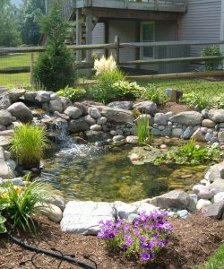 pond-stone-waterfall-mulch-flowers-500x600